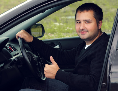 man-with-thumbs-up-in-car